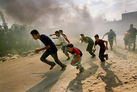 Palestinian children running from Israeli bomb blasts