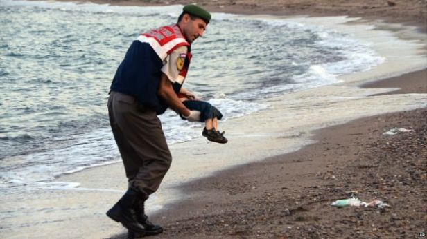 The body of Aylan is removed after being washed up on a Turkish beach.