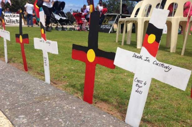 Protesters in Geraldton, WA behind a row of crosses representing Aboriginal deaths in custody